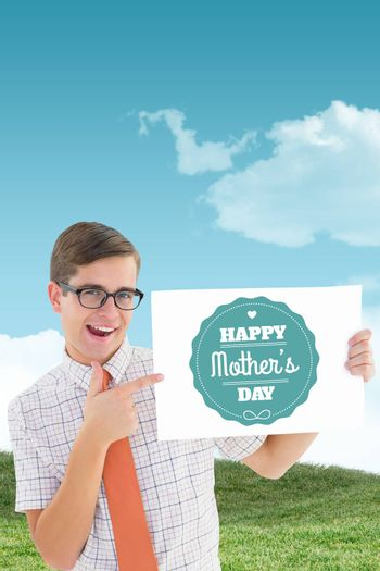 Geeky hipster smiling and showing card against field and sky
