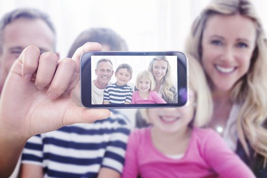 Hand holding smartphone showing against portrait of a smiling family sitting on sofa