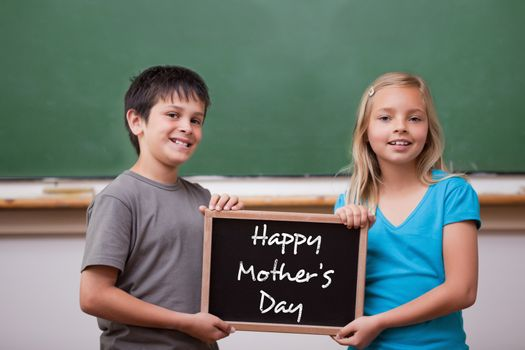 Mothers day greeting against cute pupils showing chalkboard