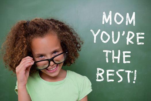Cute pupil tilting glasses against green chalkboard