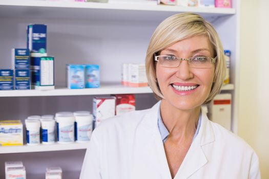 Smiling pharmacist in lab coat looking at camera