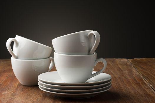 Four plain white ceramic coffee cups