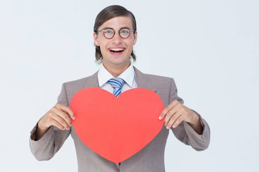 Geeky businessman smiling and holding heart card on white background