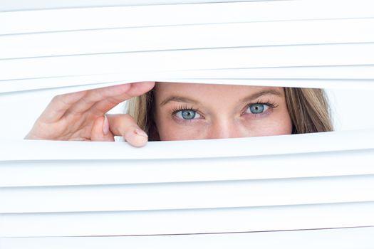 Woman peering through roller blind