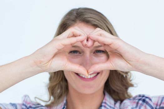 Smiling hipster doing heart shape with her hands on white background
