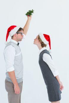 Geeky hipster kissing under mistletoe