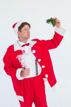 Geeky hipster in santa costume holding mistletoe