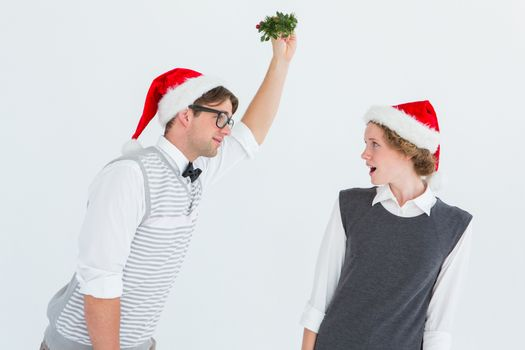 Geeky hipster holding mistletoe