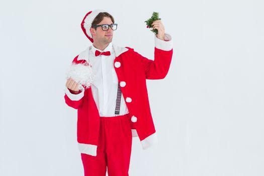 Geeky hipster in santa costume looking at mistletoe