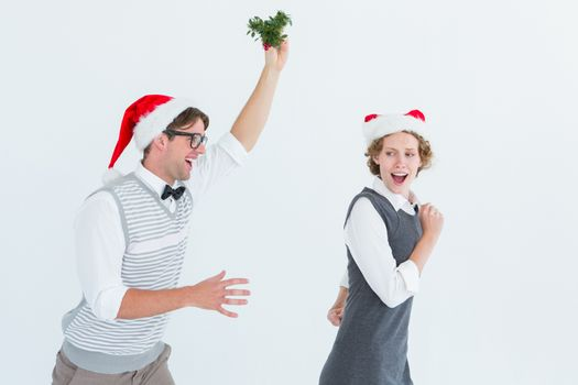 Geeky hipster running away from a man with mistletoe