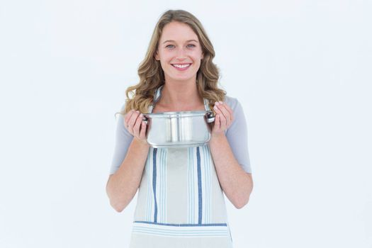 Smiling woman holding saucepan