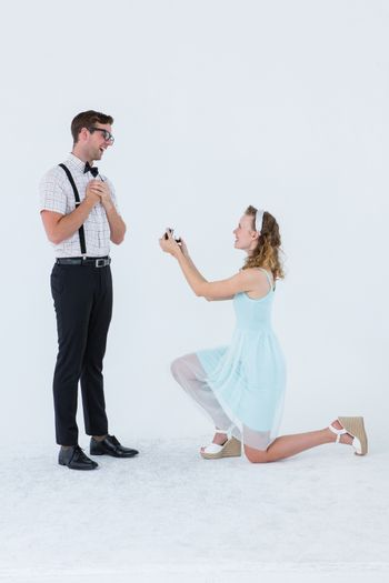 Hipster woman doing a marriage proposal to her boyfriend