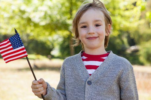Cute little boy waving american flag