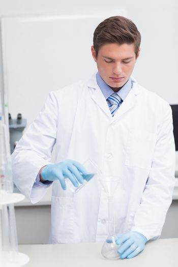 Scientist pouring chemical product in funnel