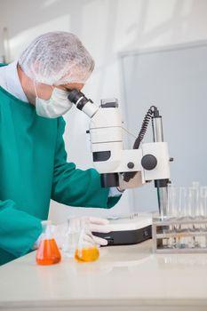 Scientist in scrubs using microscope