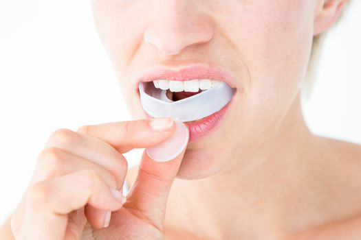 Woman putting her gum shield on white background