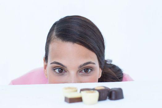 Pretty brunette peeking at chocolate