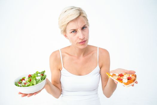 Pretty woman deciding between pizza and salad