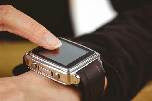 Businesswoman using her smart watch