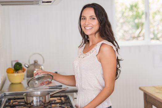 Beautiful brunette looking at saucepan