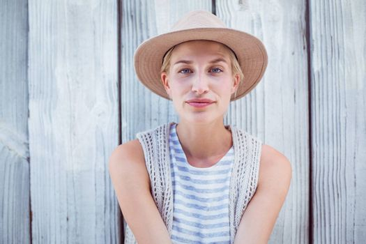 Pretty blonde woman wearing hat and smiling at camera on wooden background