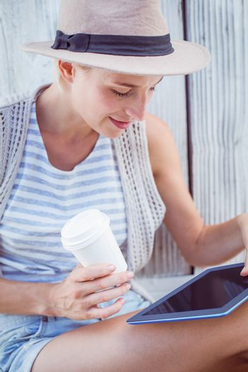 Pretty blonde woman using her tablet and holding goblet