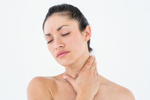 Sick brunette having throat pain