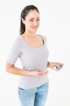 Diabetic brunette holding blood glucose monitor