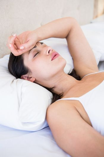 Pretty brunette with migraine on bed