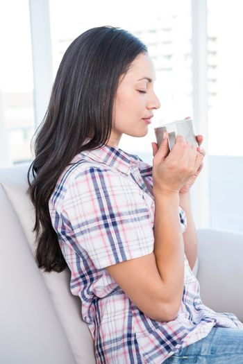 Pretty brunette holding hot beverage on couch