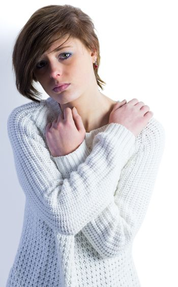Sad pretty brunette looking at camera with arms crossed