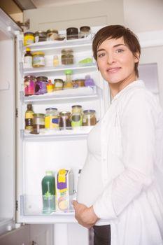 Pregnant woman opening the fridge