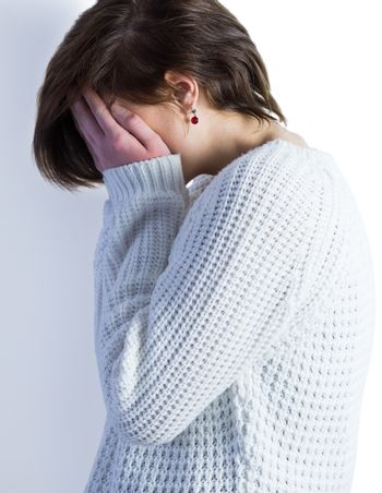 Sad pretty brunette crying with head on hands