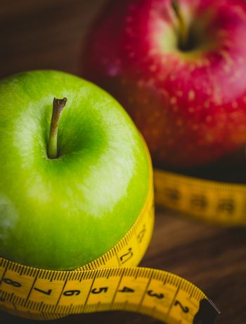 Green and red apples with measuring tape