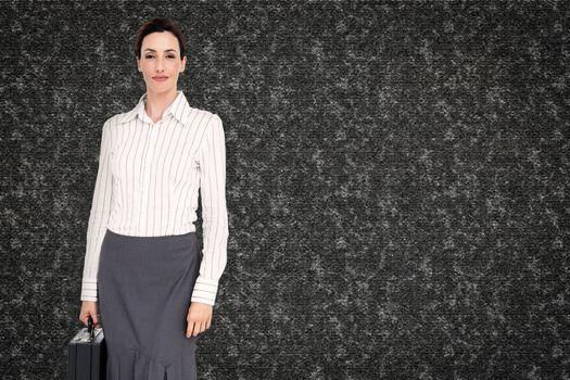 businesswoman holding briefcase against black background