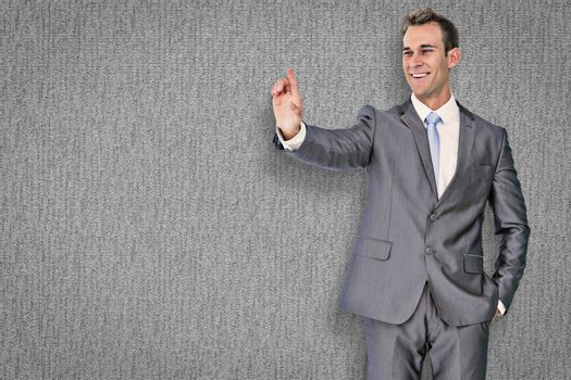 Businessman pointing against grey background
