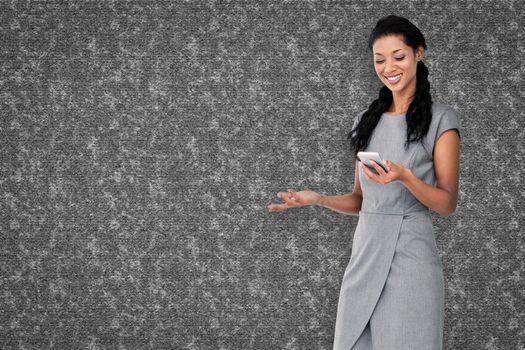 Businesswoman using smartphone  against grey background