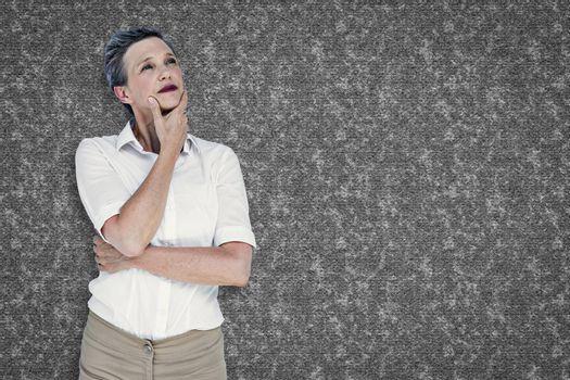 Businesswoman thinking against grey background