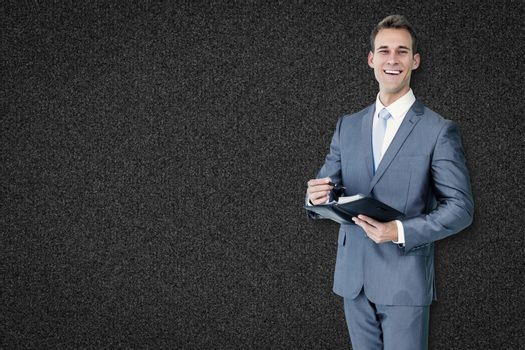 Businessman with diary against black background