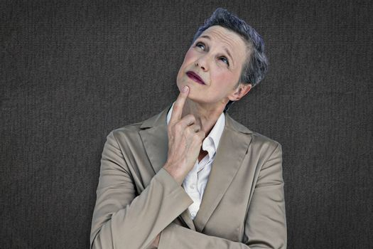 Businesswoman thinking against grey background