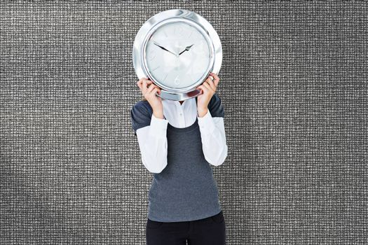 Woman holding clock in front of her head  against grey background