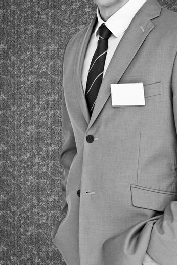 Businessman with badge against grey background