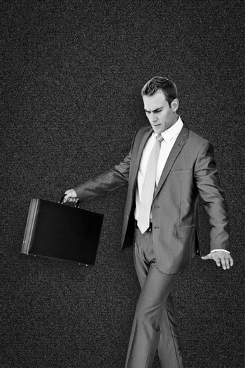 Businessman walking with his briefcase against black background