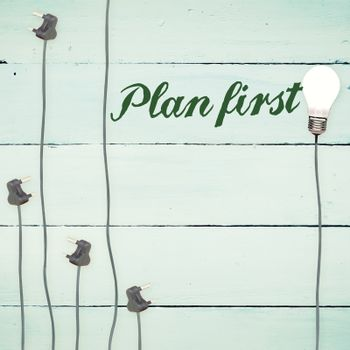 Plan first against light bulbs on wooden background