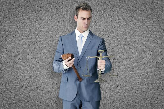 Businessman holding scales of justice against grey background