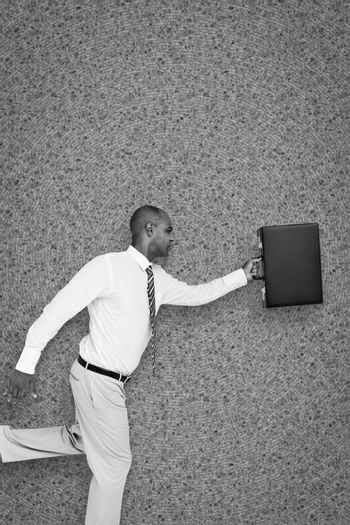 Businessman running with briefcase against grey background