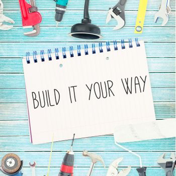 Build it your way against tools and notepad on wooden background