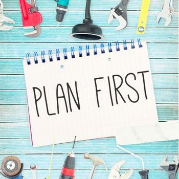 Plan first against tools and notepad on wooden background
