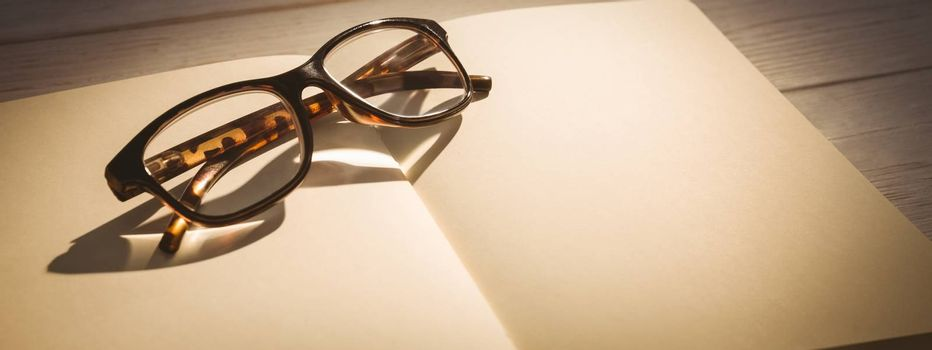 Empty notepad with reading glasses on a desk