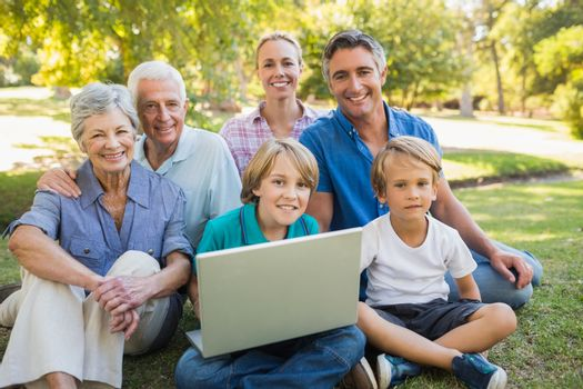 Happy family smiling at camera and using laptop in the park on a sunny day